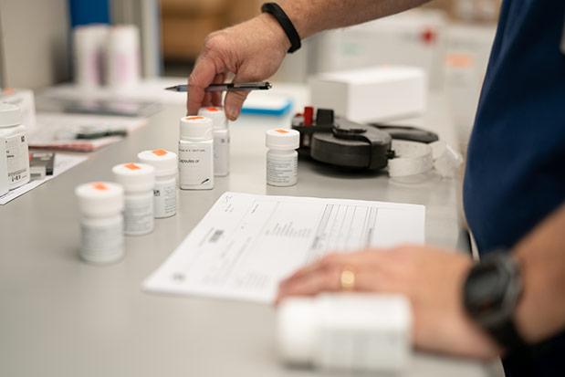 employee assessing bottles of medication